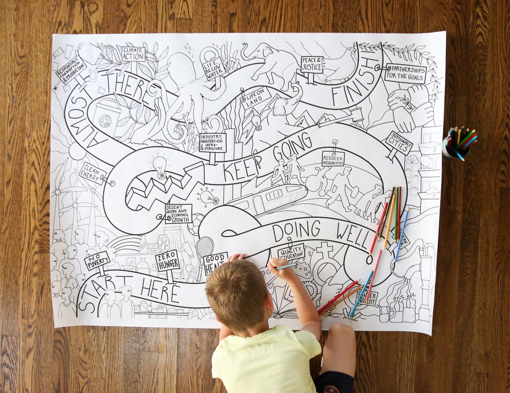 a young boy coloring a large printed coloring poster on the floor with colored pencils