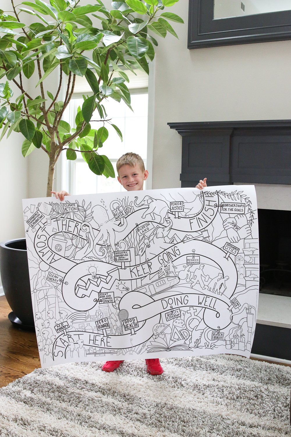 a young boy holding a large coloring poster in a living room